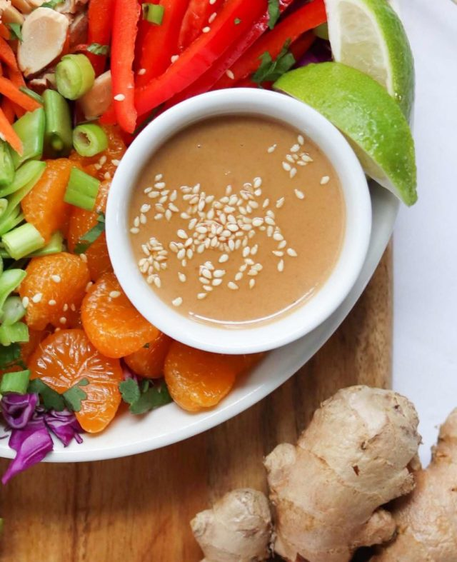Close up shot of Orange Tahini Salad Dressing in a small white bowl topped with sesame seeds.