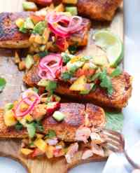 Salmon fillets on a cutting board, topped with peach salsa.
