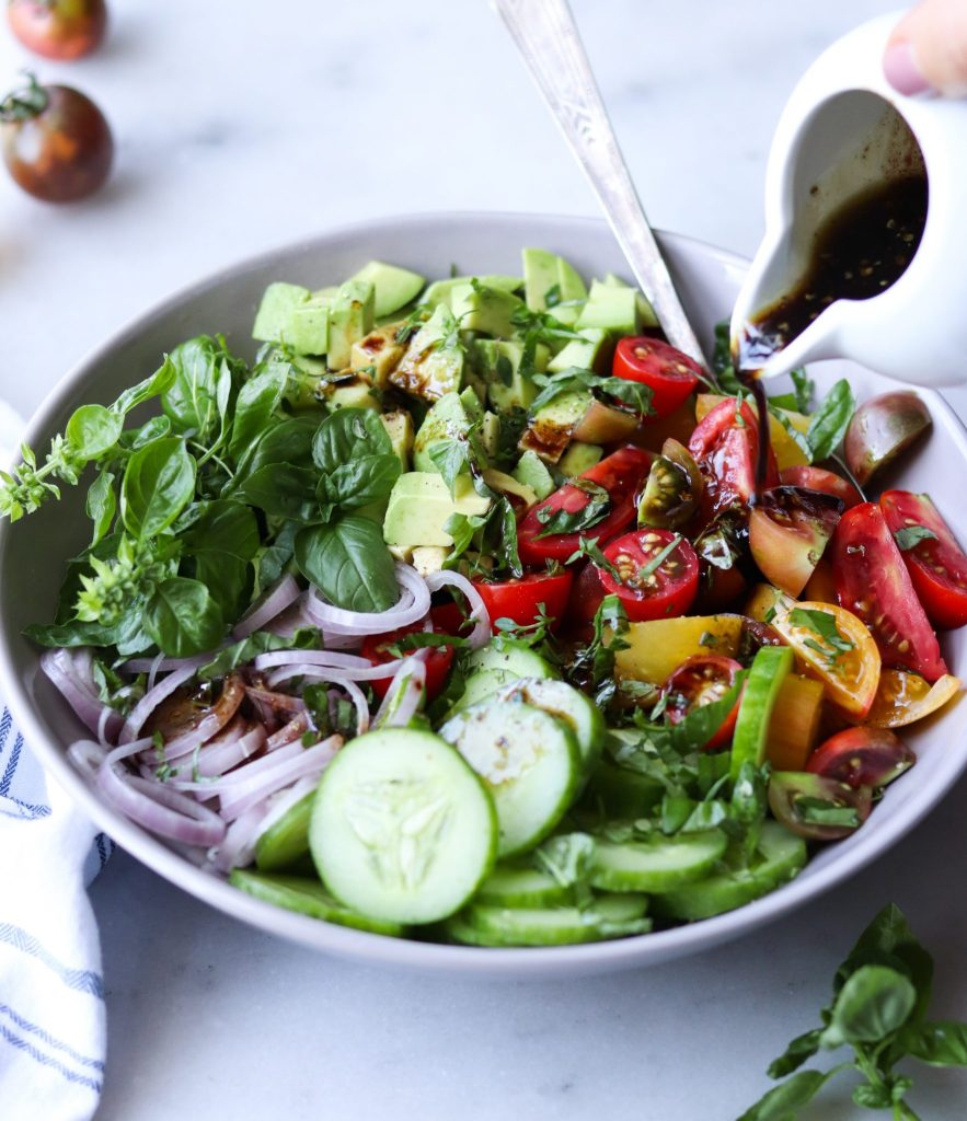A hand pouring a small pitcher of balsamic vinaigrette over the plated salad in a large bowl.