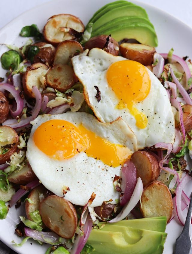 The finished dish topped with two runny fried eggs and avocado slices.