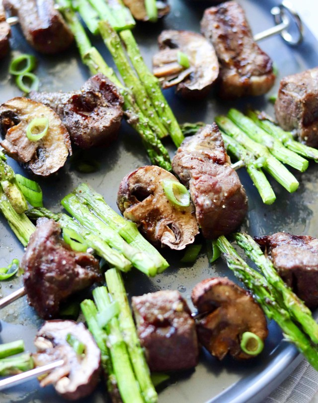 Keto/Whole30 Asian Beef and Asparagus Kebabs, plated on a dark blue dish.