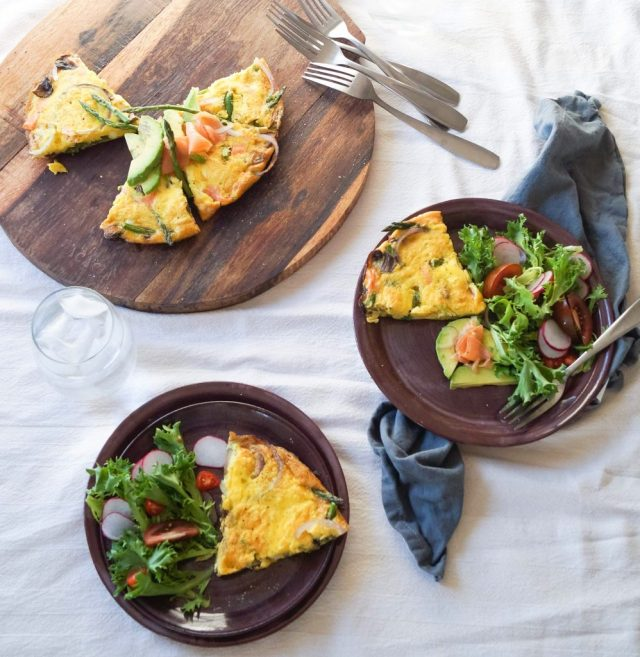 Smoked Salmon and Asparagus Frittata, finished and plated in two dishes, served with a side salad.