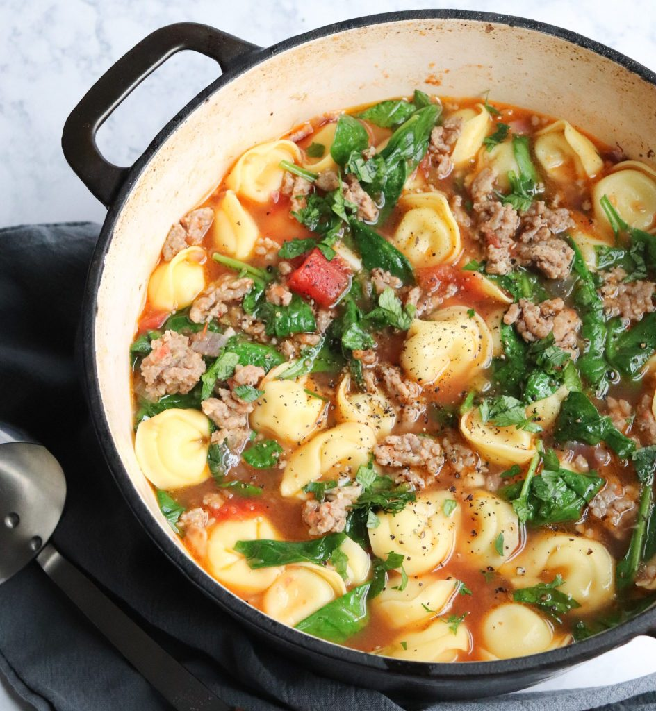 A dutch oven filled with sausage and tortellini soup.