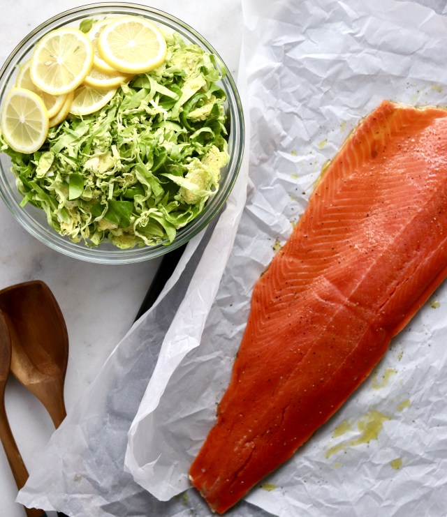 A prep shot with a bowl full of shredded Brussels sprouts and lemon slices and a whole salmon side laid out on parchment paper, drizzled with olive oil.