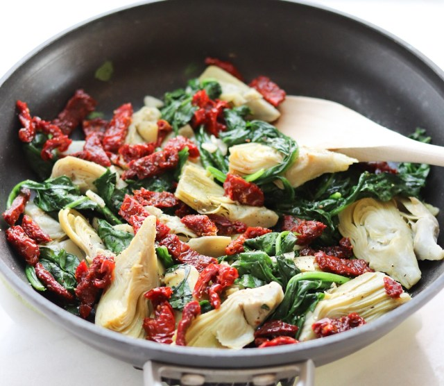 Sautéed artichokes, spinach, and sundried tomatoes in a black skillet.