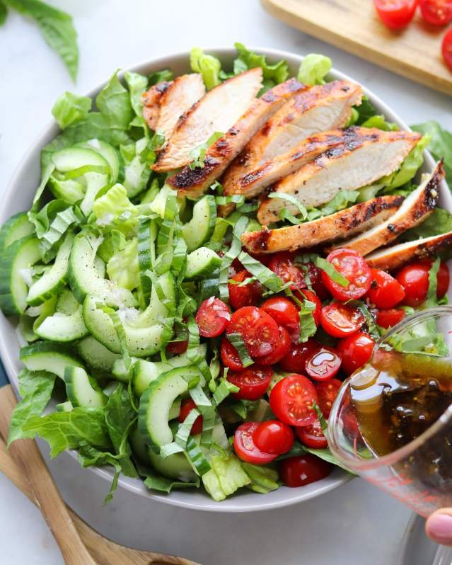 A hand holds a glass measuring cup filled with the balsamic shallot vinaigrette, drizzling the dressing over the finished tomato basil marinated grilled turkey salad.