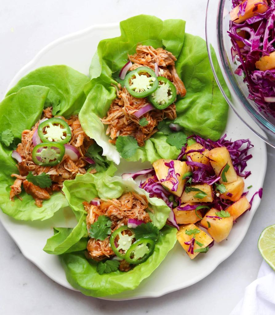 A white plate with three lettuce cups filled with bbq chicken and topped with sliced jalapeno. A hand squeezes a lime on top.