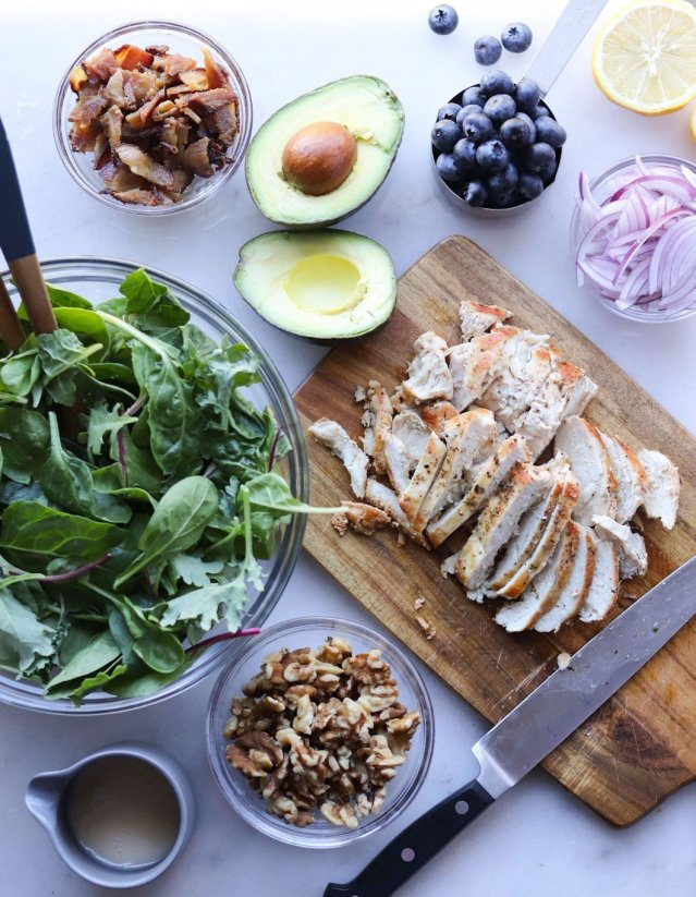 Grilled Chicken Salad Ingredients laid out on a white marble board: Greens in a large glass bowl, chopped crispy bacon, blueberries, sliced grilled chicken, walnuts, and avocado.