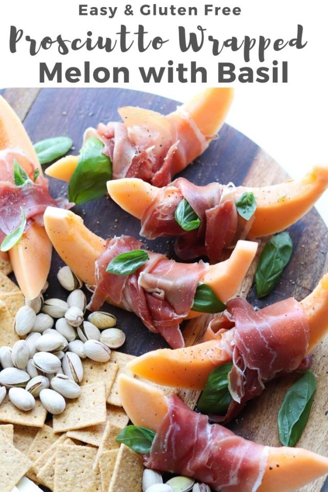 "Close up of a wooden cutting board topped with prosciutto wrapped melon, and pistachios with the text, ""Easy and Gluten Free Prosciutto Wrapped Melon with Basil."""