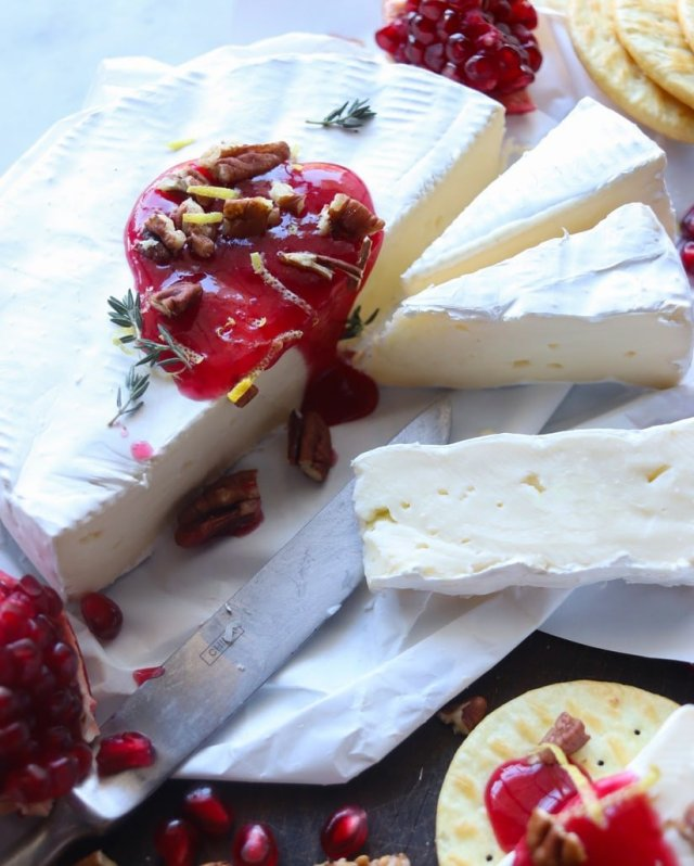 Close up of a round of brie, with half of it cut into segments. The wheel is drizzled with cranberry horseradish brie, pecans, and lemon zest.