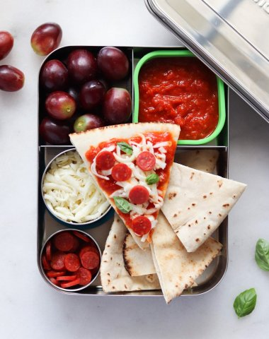 A lunch box filled with sliced pita, sauce, mini pepperoni, mozzarella cheese, and grapes.