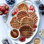 Paleo Waffles laid out on a white serving dish, surrounded by small dishes with all the toppings.