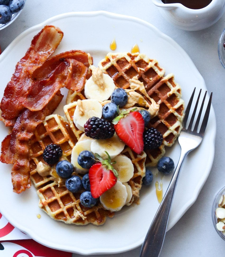 Finished Paleo Waffles plated on a white plate, topped with berries and maple syrup, served with a side of bacon.