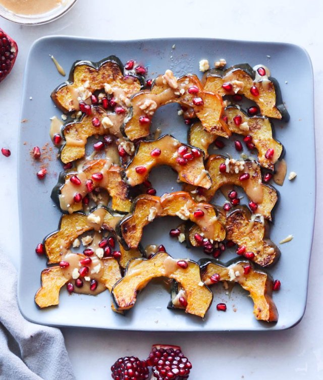 Roasted Acorn Squash recipe with a Maple Almond Butter drizzle and pomegranate seeds and cinnamon sprinkled on top.