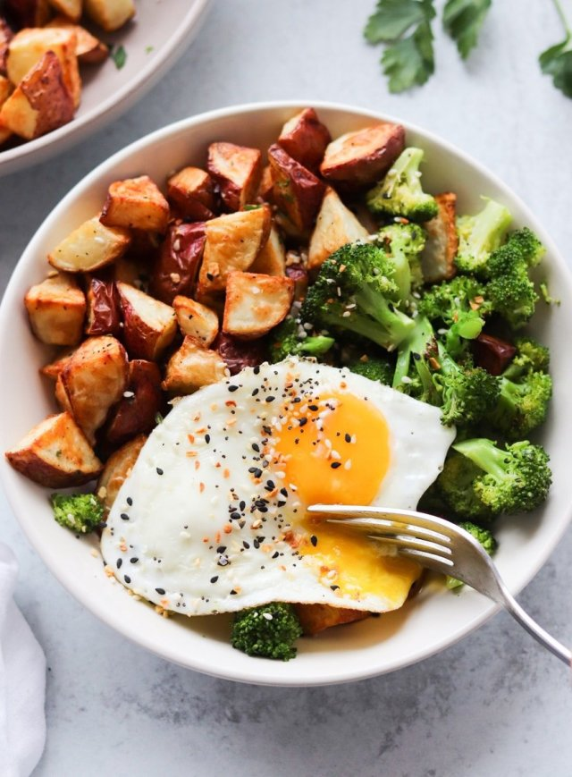 A white bowl with diced potatoes, broccoli, and a fried egg with a fork cutting into the egg.