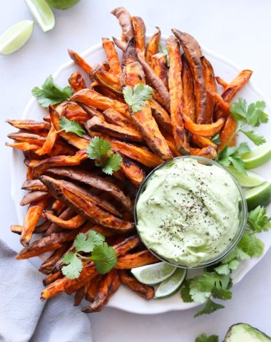 Cooked crispy sweet potato fries arranged on a white plate with a small glass dish of avocado aioli. The fries are sprinkled with black pepper and cilantro leaves and there are a few lime slices arranged on the plate.