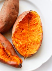 A cooked microwaved sweet potato on a white plate, cut open to show the soft insides!