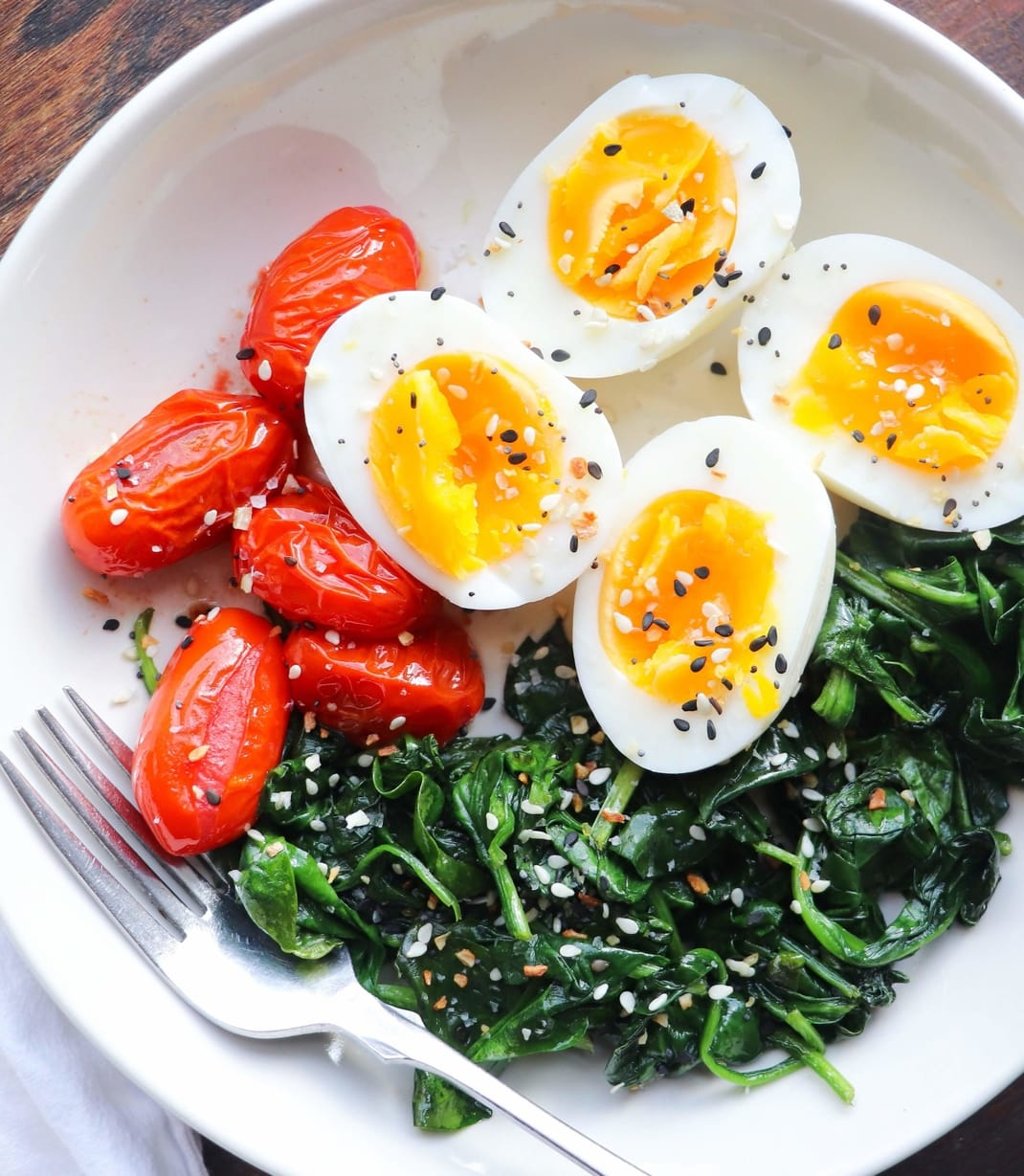 A white bowl with cut soft boiled eggs, sautéed spinach, and cherry tomatoes (Whole30, Paleo, Gluten Free friendly).