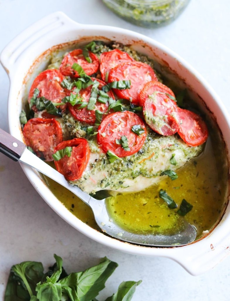 A large serving spoon set inside a white oval baking dish, with the finished pesto chicken cooked inside and topped with sliced tomatoes and fresh basil.