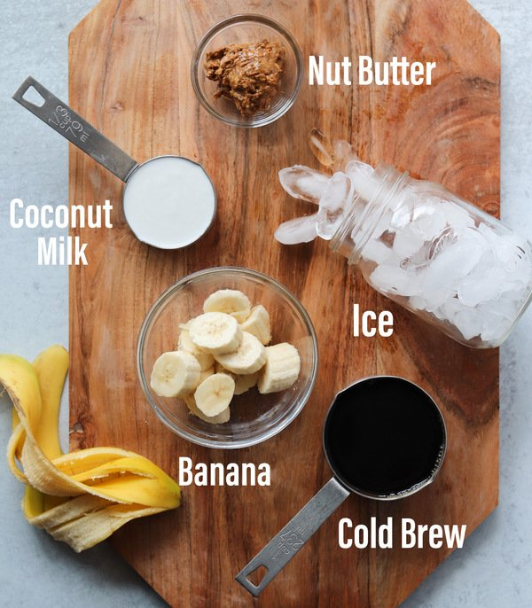 All of the banana, almond, and coffee smoothie ingredients laid out on a cutting board and labeled.