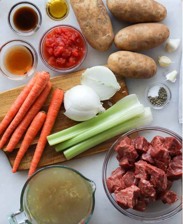 The beef stew ingredients, laid out on a white marble board.