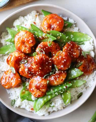 Close up top down of a large bowl filled with rice, topped with cooked snow peas and shrimp, garnished with sesame seeds.