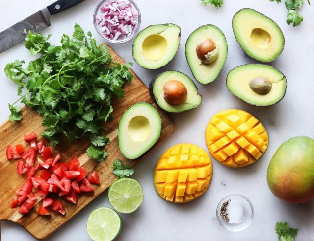 All of the ingredients laid on a white marble board: cilantro, red onion, tomato, mango, lime, avocado, and salt and pepper.