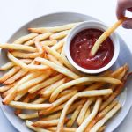 "A photo of plated fries and ketchup with the text ""Perfect Air Fryer Frozen French Fries"" for Pinterest"