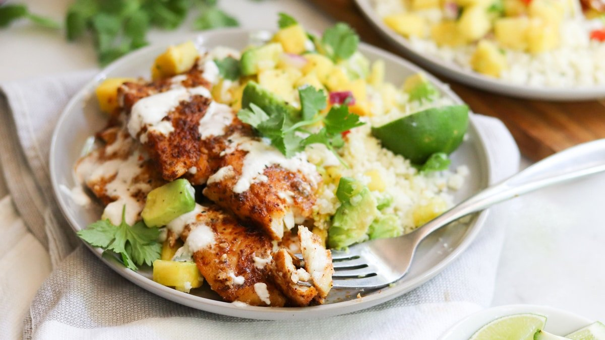 A small gray plate filled with cooked blackened flounder that's drizzled with cream and served with pineapple salsa and cauliflower rice.