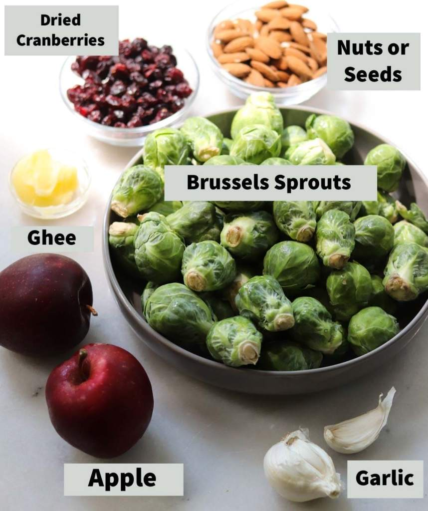 All of the salad ingredients with labels on a white marble board - Brussels sprouts, dried cranberries, nuts or seeds, apple, ghee, and garlic.