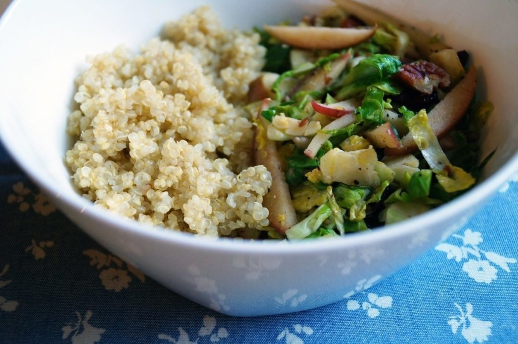 Close up side view of the finished salad served in a white bowl with quinoa.