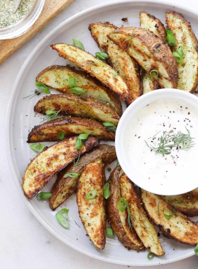 Crispy air fryer potato wedges arranged on a gray plate with a small dish of ranch, sprinkled with sliced green onions.