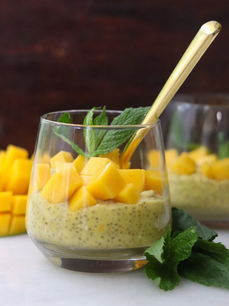 Side view of a small glass filled with mango chia pudding, topped with diced mango and mint leaves.