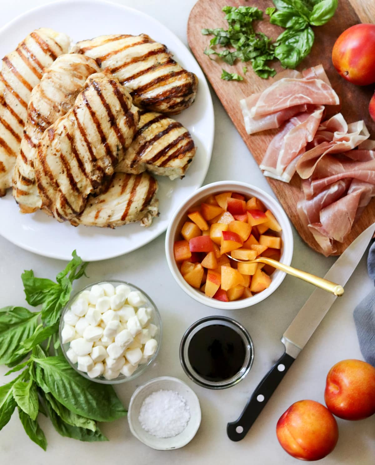 A white marble board with the recipe ingredients laid out: Grilled chicken breasts, prosciutto, basil, mozzarella pears, balsamic vinegar, and a bowl of diced apriums.