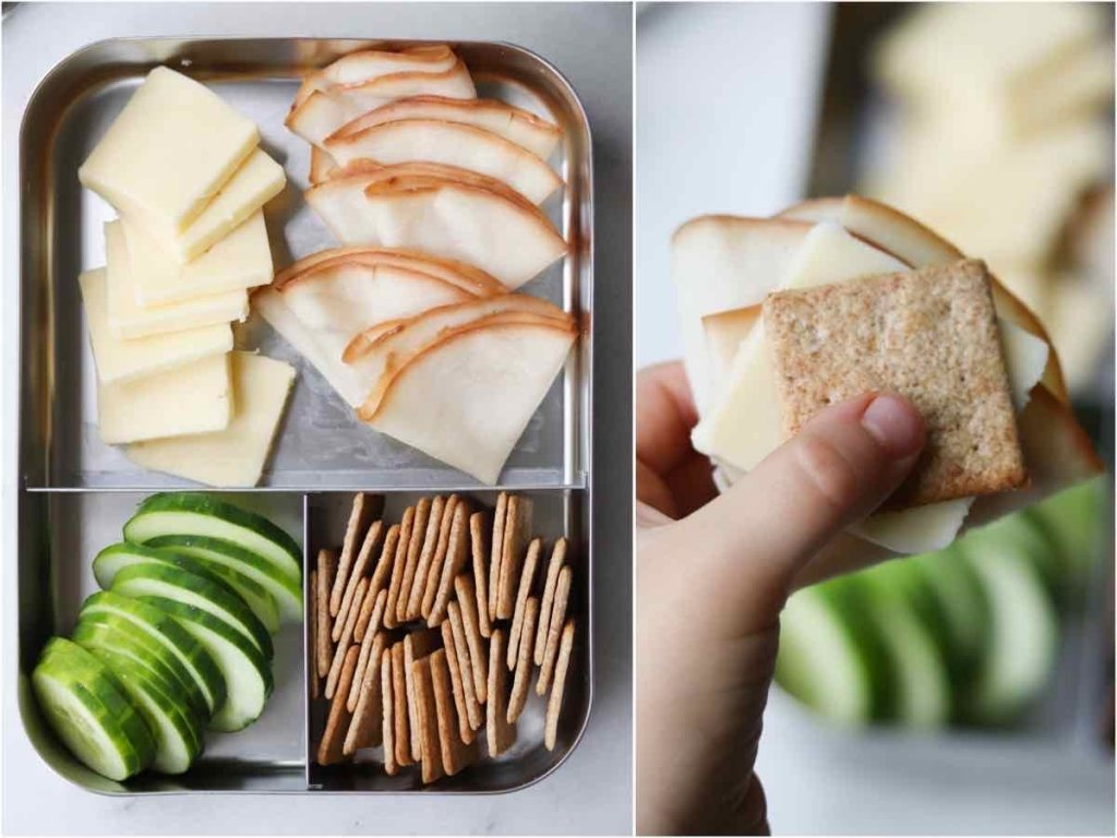 Collage of a lunch box filled with sliced cheese, deli turkey, crackers, and sliced cucumbers, and a close up of a kids' hand holding an assembled cracker sandwich.