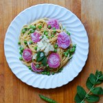 Top down of a white plate on a wooden cutting board, filled with spaghetti, sliced rainbow beets, and peas, topped with extra parmesan and peas.