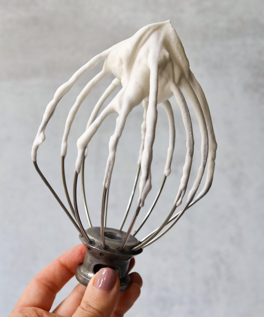 Hand holding the whisk attachment from a stand mixer dipped in whipped cream.