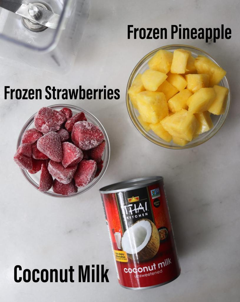 Frozen pineapple and frozen strawberries in small glass dishes and a can of coconut milk, labeled on a white board.