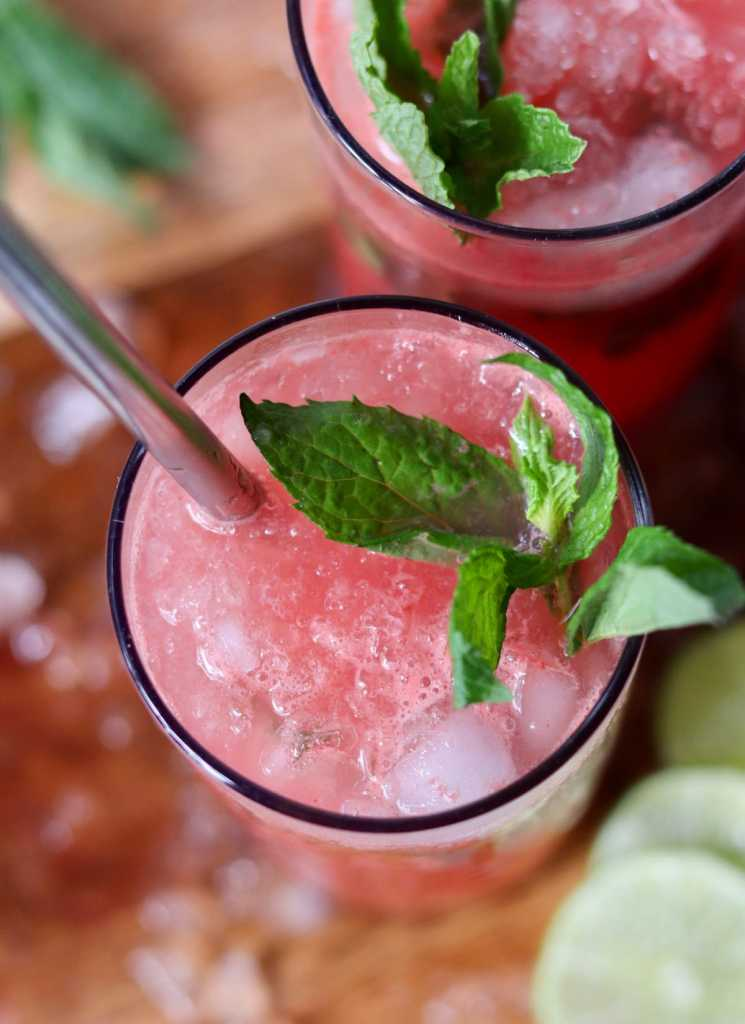 Close up top down of a tall glass filled with ice and watermelon-lime juice, garnished with fresh mint.