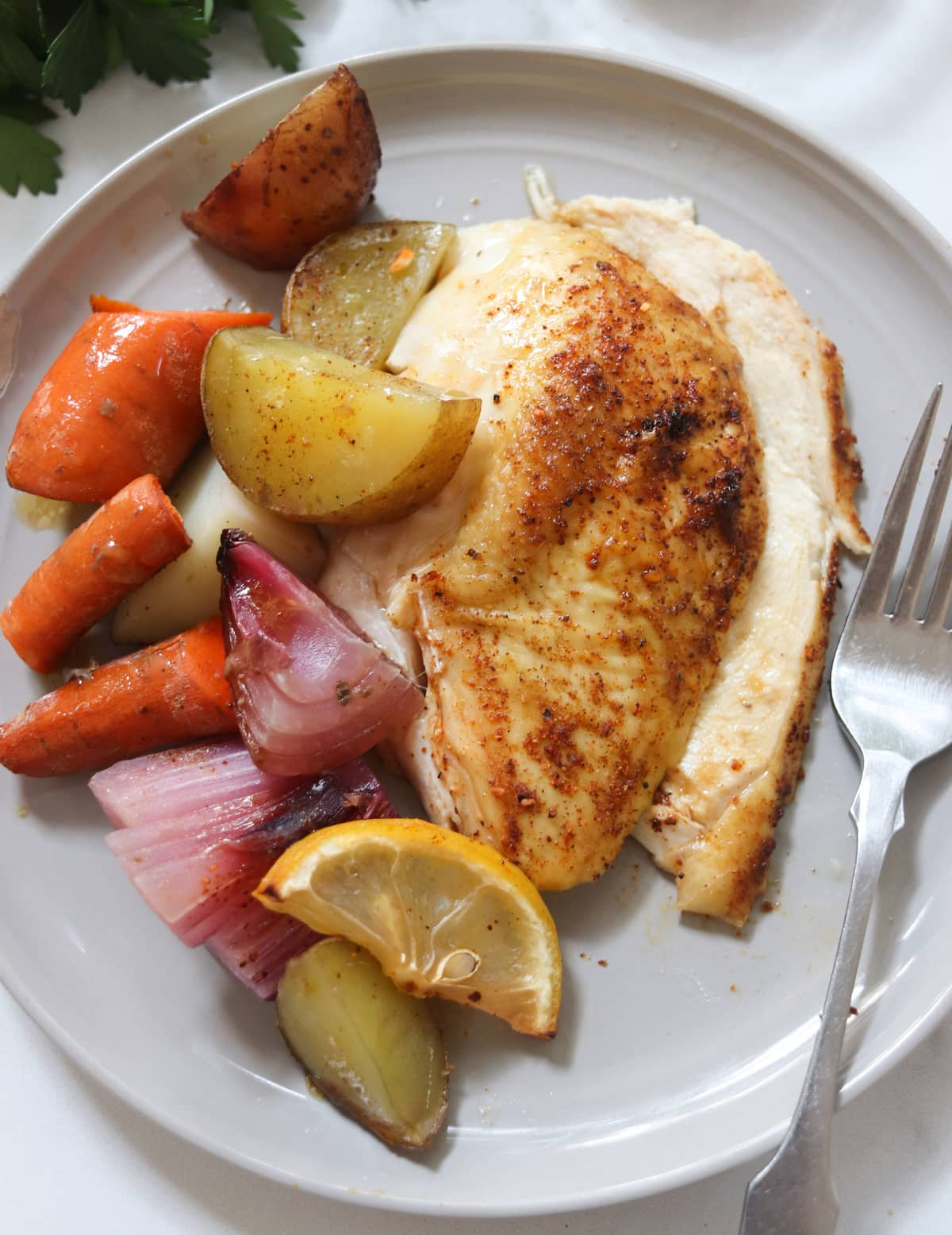 Two slices of cooked chicken breast on a small gray plate with roasted vegetables.