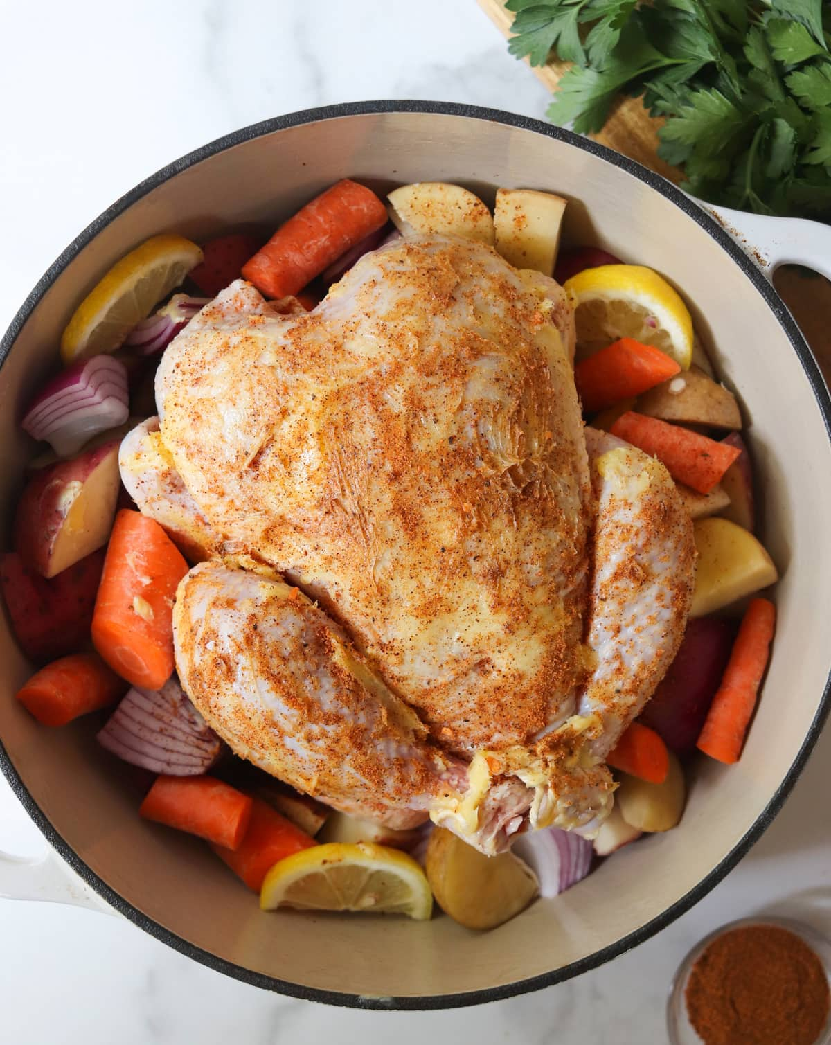 The uncooked chicken resting on top of sliced vegetables inside the dutch oven.
