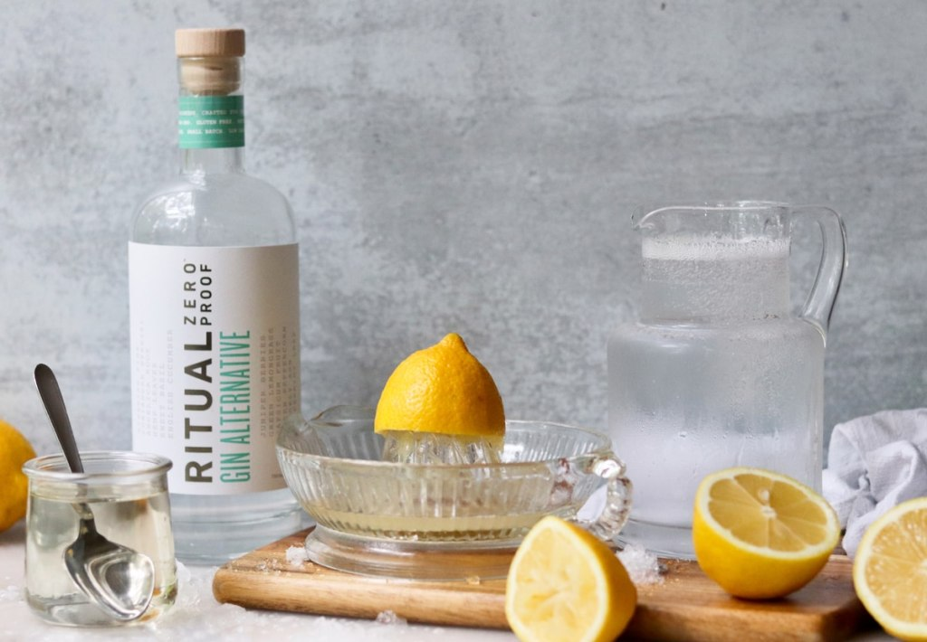 Recipe ingredients laid out on a marble board: Nonalcoholic gin, simple syrup, club soda, and freshly squeezed lemon juice.
