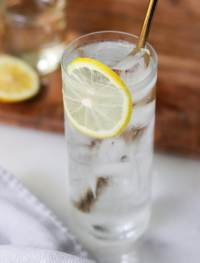 Close up of a tall glass filled with large ice cubes, a clear Tom Collins mocktail, garnished with a slice of lemon.