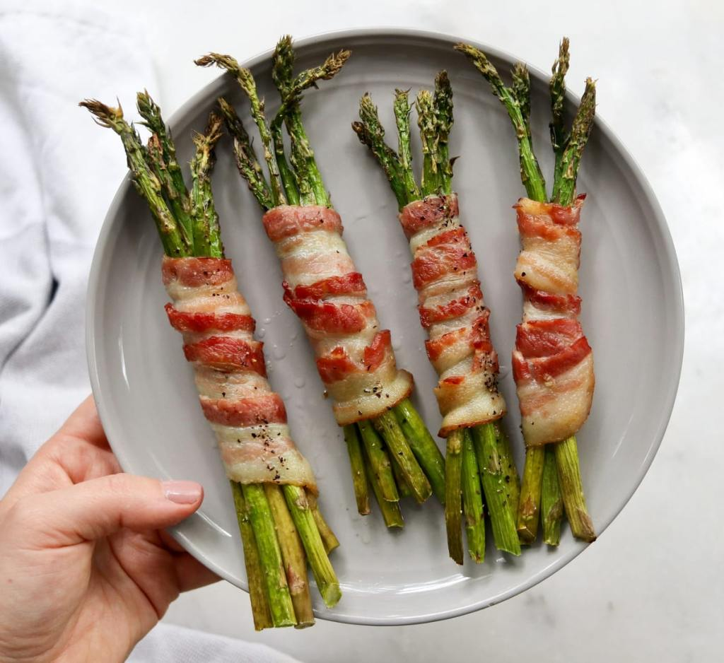 A hand holding a small gray dish with four finished bundles of bacon wrapped asparagus.