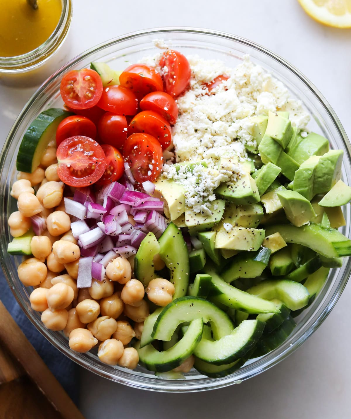 Top down of the salad ingredients arranged in a large bowl, not yet tossed together.