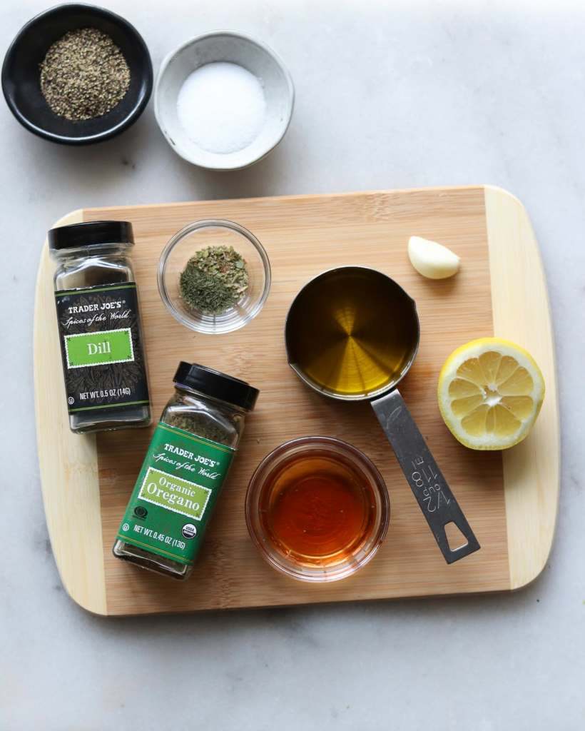 The salad dressing ingredients laid out on a small wooden cutting board: dill, oregano, oil, lemon, red wine vinegar, garlic, and salt and pepper.