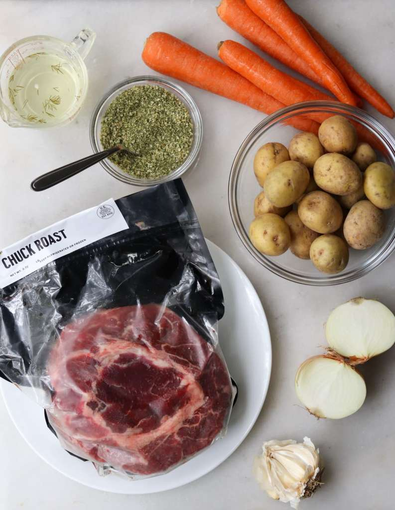 Recipe ingredients laid out on a white marble board: a chuck roast, pickle juice, ranch seasoning, carrots, onion, garlic, and baby potatoes.