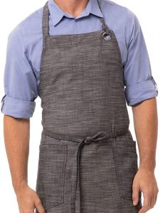 A man wearing a gray apron with a tie around the waist.