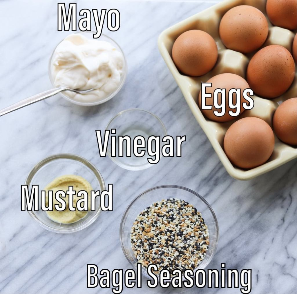 The recipe ingredients laid out in small glass dishes on a marble board and labeled: mayo, eggs, vinegar, mustard, everything bagel seasoning.