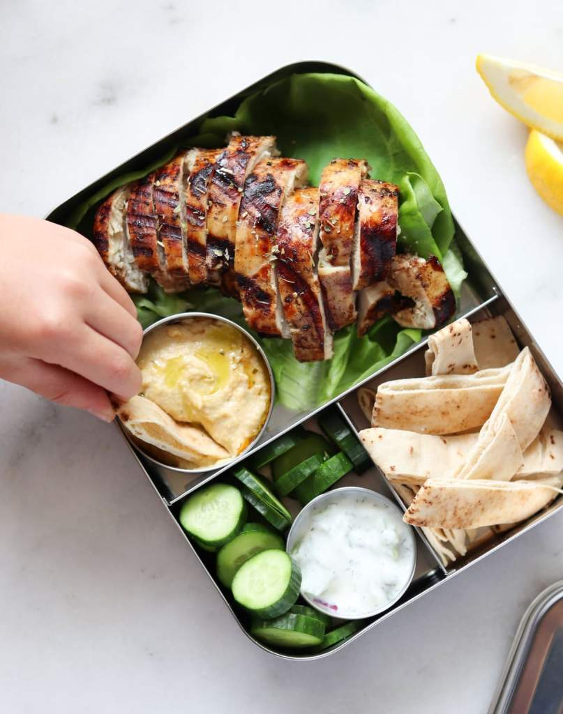 A kid's hand dipping bread into hummus, served with sliced baby cucumbers, and sliced grilled chicken.